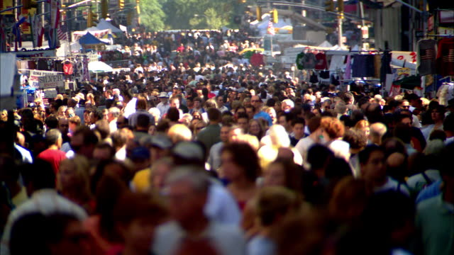 DEFOCUS wide shot crowds walking through street fair / NYC