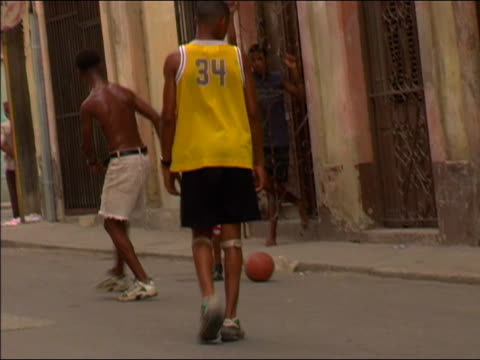 vidéos et rushes de 2003 wide shot cuban boys playing soccer with a basketball on the street / cuba - jeunes garçons