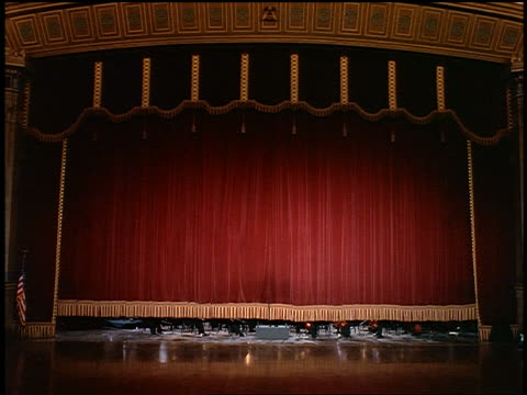 wide shot curtain rising in concert hall to reveal orchestra