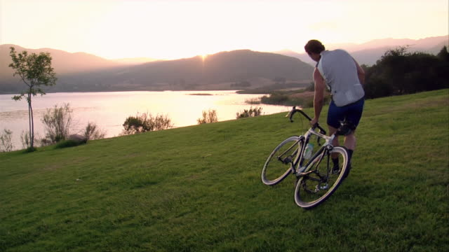Wide shot cyclist setting his bike down in the grass / sitting down and watching the sun set over a lake
