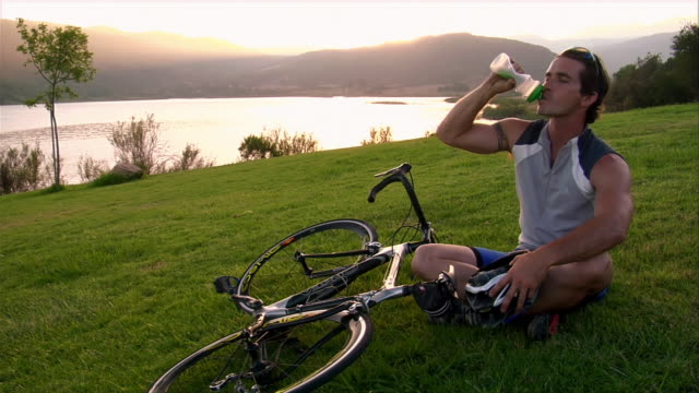 wide shot cyclist sitting on grass and drinking from water bottle / sun setting over lake in background / standing up and walking away with bike - ein mann allein stock-videos und b-roll-filmmaterial