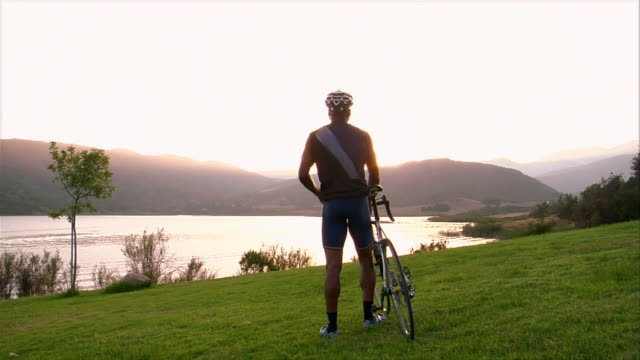 vidéos et rushes de wide shot cyclist walking his bike in grass and taking off helmet / watching the sun set over a lake - seulement des hommes d'âge mûr