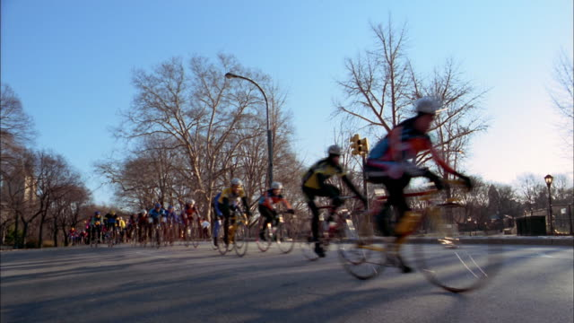 wide shot cyclists riding on road in central park - anno 2001 video stock e b–roll