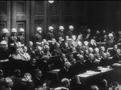 vídeos de stock, filmes e b-roll de wide shot defendants + military police in courtroom at war crimes trials / nuremberg / newsreel - 1946