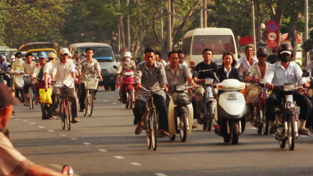 wide shot dense traffic with many cyclists moving through ho chi minh city / vietnam - pollution mask stock videos and b-roll footage
