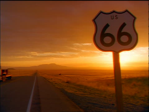 vidéos et rushes de wide shot desert road + plain at sunset with route 66 road sign in foreground / southwest us - route 66