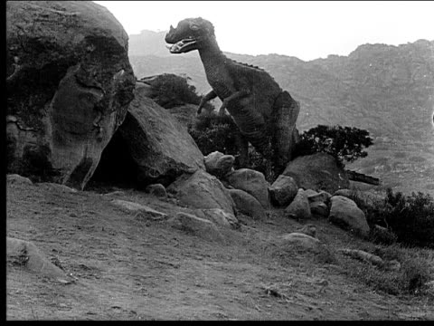 1914 b/w wide shot dinosaur eating outside cave entrance - 1914 stock videos & royalty-free footage