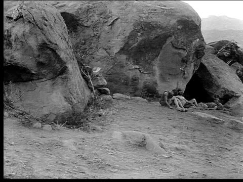 1914 B/W Wide shot Dinosaur eating outside cave entrance while two cavemen sleep nearby