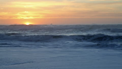 wide shot directly into sun of waves crashing on pacific ocean beach during golden sunset. - horizon over water stock videos & royalty-free footage