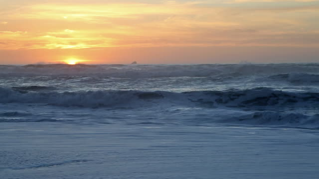 vidéos et rushes de wide shot directly into sun of waves crashing on pacific ocean beach during golden sunset. - ligne d'horizon au dessus de l'eau