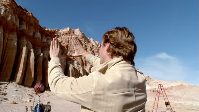 wide shot director using hands to frame shot of cliffs on desert film set / red rock canyon state park, california - film director stock videos & royalty-free footage