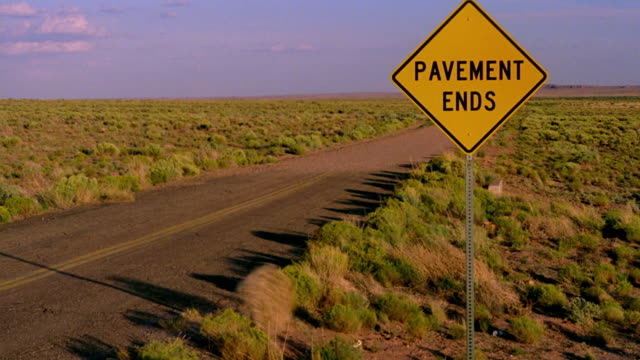 """Wide shot dirt road in desert with sign reading """"pavement ends"""" and tumbleweed rolling across / Holbrook, Arizona"""