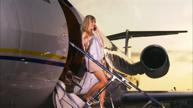 vídeos de stock, filmes e b-roll de wide shot diva exiting private airplane, talking on cell phone, and leading chihuahua down steps / long beach, california, usa - celebridade