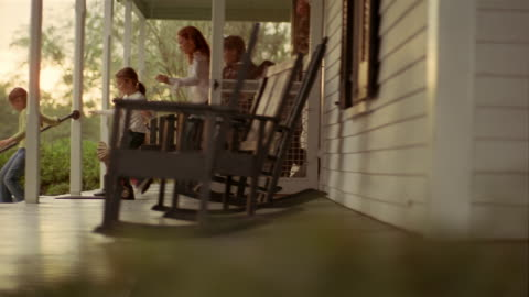 wide shot dolly shot across porch/ chilren leaving house and running down front steps of porch/ boy jumping off steps - porch stock videos & royalty-free footage