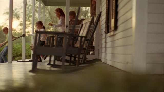Wide shot dolly shot across porch/ chilren leaving house and running down front steps of porch/ boy jumping off steps