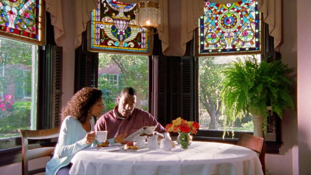wide shot dolly shot black couple eating breakfast and reading newspaper together - breakfast stock videos & royalty-free footage