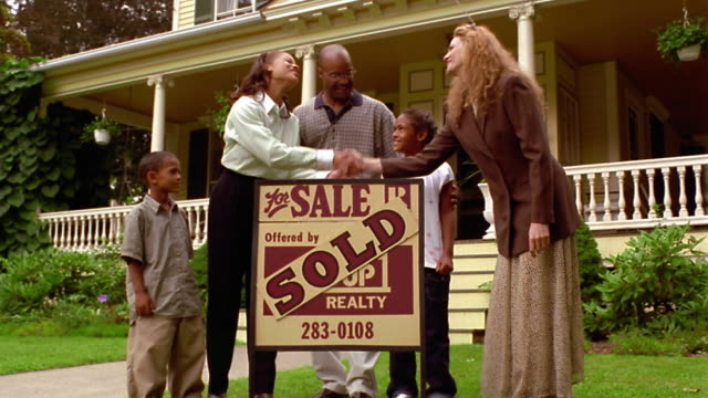 wide shot dolly shot black family standing with female real estate agent in front of house with 'sold' sign / shaking hands - real estate sign stock videos & royalty-free footage
