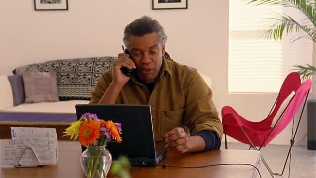 wide shot dolly shot black man at laptop in living room / on phone discussing bills - sladdlös telefon bildbanksvideor och videomaterial från bakom kulisserna