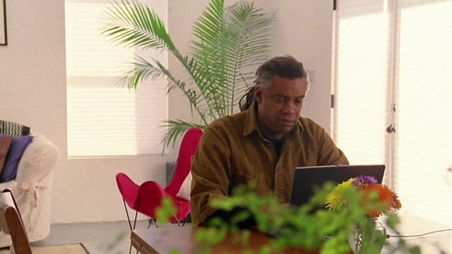 Wide shot dolly shot Black man typing on laptop computer in living room