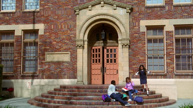 wide shot dolly shot children sit on school stairs before other children exit door and join them / boy walks away - elementary school building stock videos & royalty-free footage