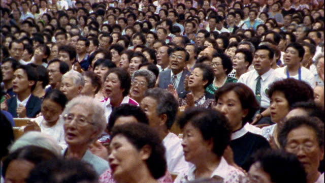 Wide shot dolly shot congregation church singing and clapping hands / South Korea
