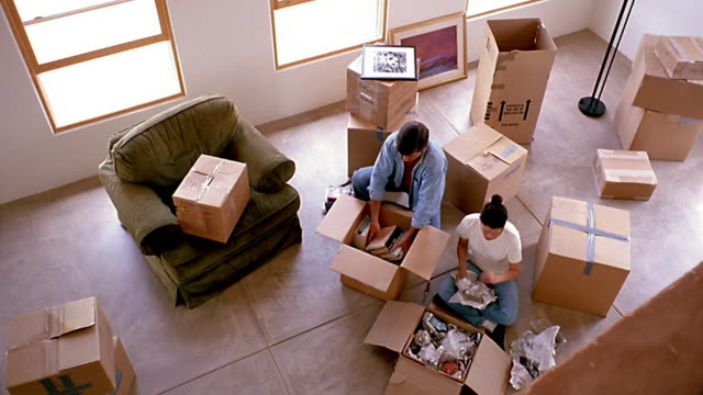Wide shot dolly shot couple sitting and unpacking boxes