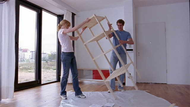 vidéos et rushes de wide shot dolly shot couple standing up shelf unit - éléments de décoration intérieure