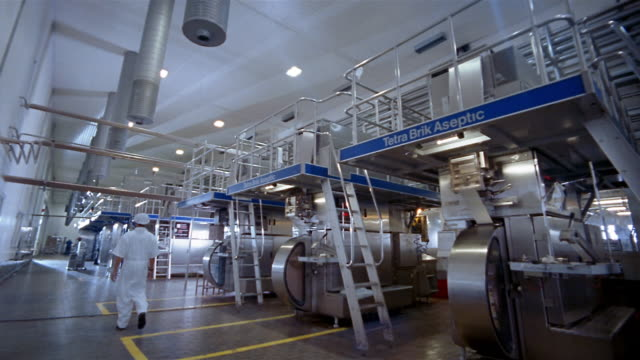 Wide shot dolly shot factory worker moving wheel of packaging past aseptic machinery at milk plant / Indonesia
