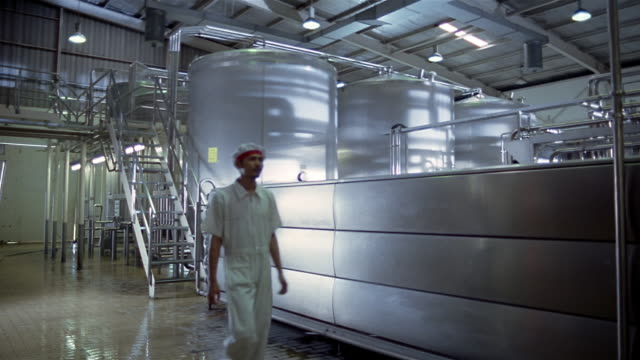 wide shot dolly shot factory worker walking past vats at dairy plant/ worker inspecting machinery in background/ indonesia - 大樽点の映像素材/bロール