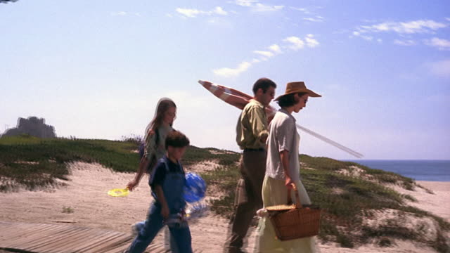 Wide shot dolly shot family walking on wooden path towards beach / girl playing with bubbles / California
