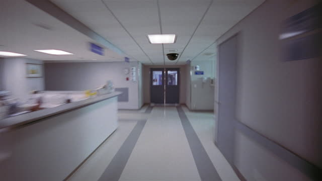 wide shot dolly shot fast motion down hospital hall through doors to nurse with newborn twins in cribs / mexico city - dolly shot stock videos & royalty-free footage