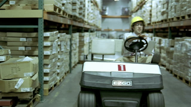 wide shot dolly shot foreman driving cart through stock warehouse - golf cart stock videos & royalty-free footage