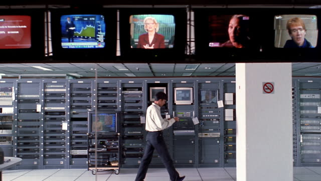 stockvideo's en b-roll-footage met wide shot dolly shot kabelvision tv control room with overhead row of monitors broadcasting tv shows / jakarta - medium filmcompositietype