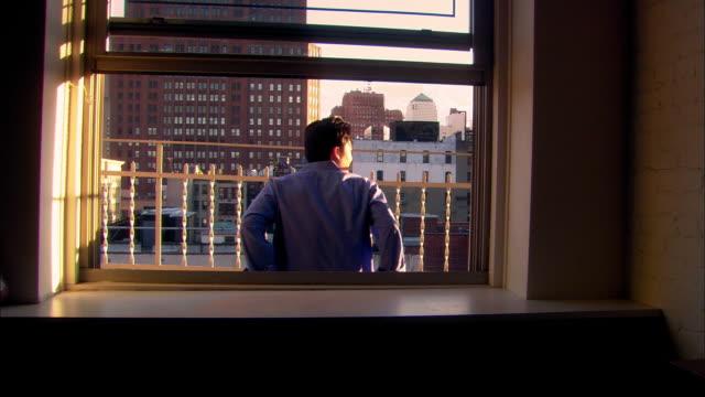 vídeos de stock, filmes e b-roll de wide shot dolly shot man sitting on balcony overlooking city / nyc - peitoril de janela