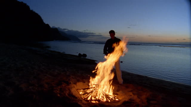 wide shot dolly shot man standing near fire on beach with water in background - lagerfeuer stock-videos und b-roll-filmmaterial
