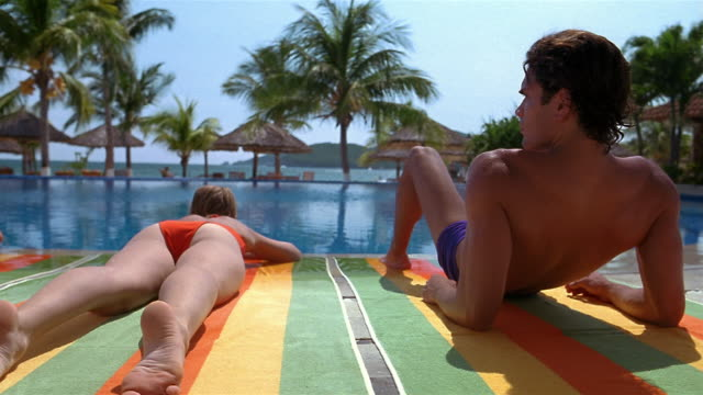 wide shot dolly shot men and women sunbathing near edge of pool with palm trees in background - sunbathing stock videos & royalty-free footage