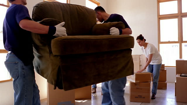wide shot dolly shot movers carrying and putting down chair with couple unpacking boxes in background - furniture stock videos & royalty-free footage