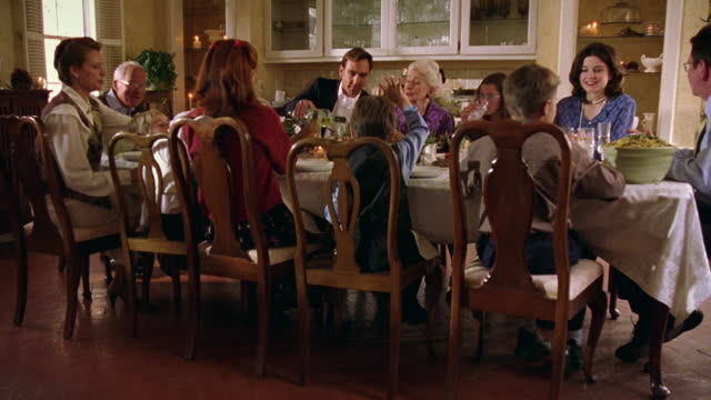 vidéos et rushes de wide shot dolly shot multi-generational family sitting at dining room table eating dinner - repas
