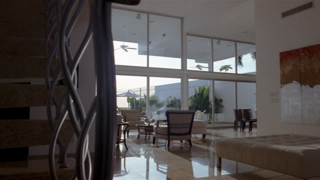 vídeos de stock, filmes e b-roll de wide shot dolly shot past bannister to living room w/ floor to ceiling windows - interior de casa modelo