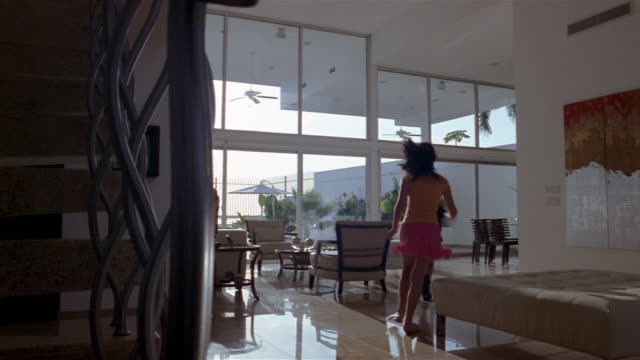 Wide shot dolly shot past bannister to living room w/ floor to ceiling windows / boy and girl running towards sliding door with father behind them / sliding door open and walking onto deck