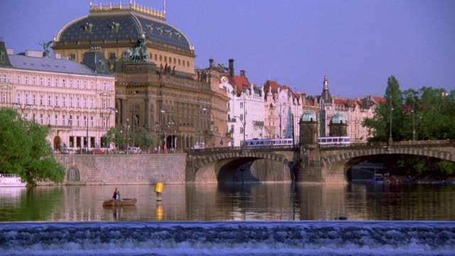 wide shot dolly shot prague national theater with buildings and bridge on vltava river / prague, czech republic - vltava river stock videos & royalty-free footage