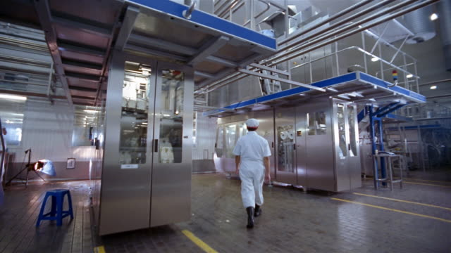 wide shot dolly shot technician opening doors to aseptic packaging chamber at milk processing plant / indonesia - food processing plant stock videos & royalty-free footage