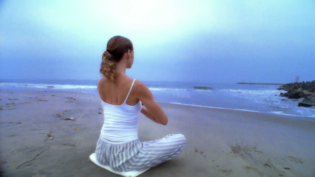 stockvideo's en b-roll-footage met wide shot dolly shot to high angle woman sitting cross-legged doing yoga on beach / los angeles - noordelijke grote oceaan