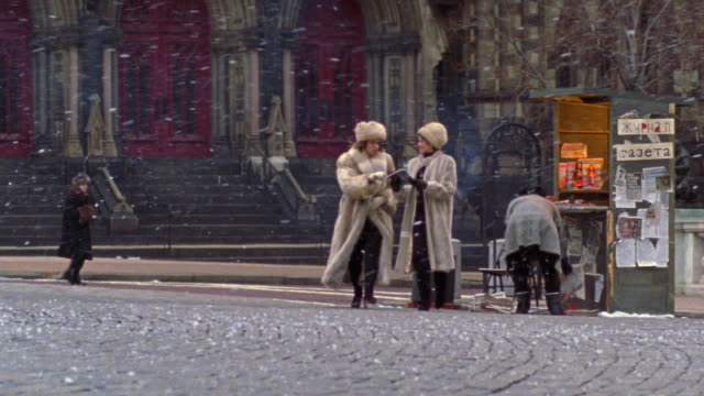 vídeos de stock e filmes b-roll de wide shot dolly shot two woman wearing fur coats + hats buying magazine from newsstand with snow falling - magazine