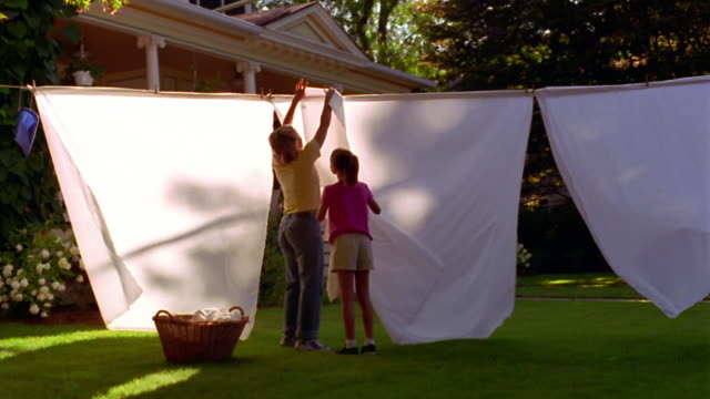 wide shot dolly shot woman + girl hanging laundry on clothesline in yard with laundry basket on grass