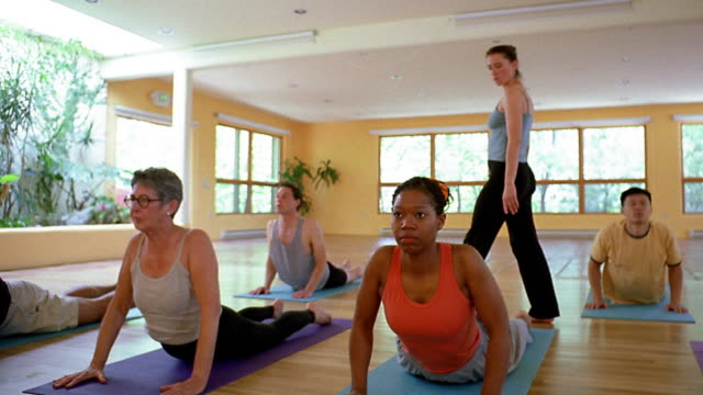 Wide shot dolly shot yoga class performing cobra and downward dog pose with female instructor inspecting + helping them