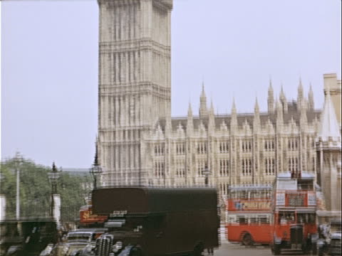 1939 Wide shot Double-decker buses and black taxis driving on busy city street near Houses of Parliament and Big Ben / Westminster, London, England, USA