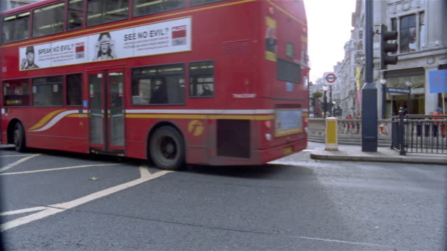Wide shot double-decker buses rounding corner of busy intersection at Oxford Circus / London, England
