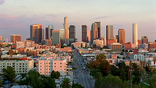 Wide shot downtown Los Angeles with skyline in background / early evening