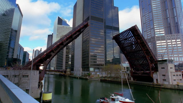 vídeos de stock, filmes e b-roll de wide shot drawbridge closing over chicago river / tilt up to sears tower - drawbridge